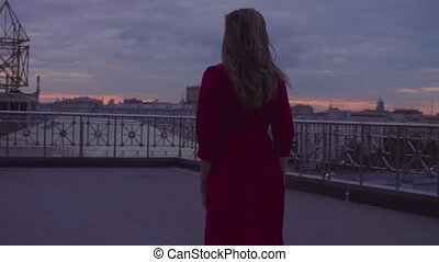 Young woman in red dress is walking on a square