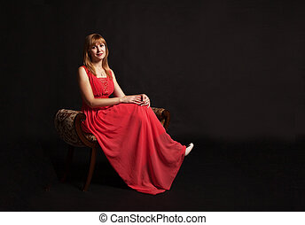 young woman in red dress sitting on a chair