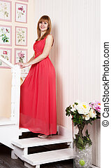 young woman in red dress standing on the stairs