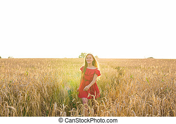 Young woman in red dress walking on a background of golden oats field, summer outdoors