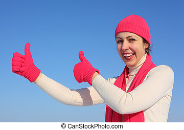 Young woman in red gloves shows gesture ok