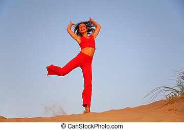 Young woman in red runs on sand