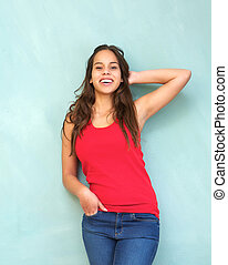 Young woman in red shirt smiling with hand in hair