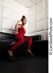 Young woman in red sitting on sofa