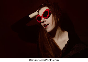 Young woman in red sunglasses