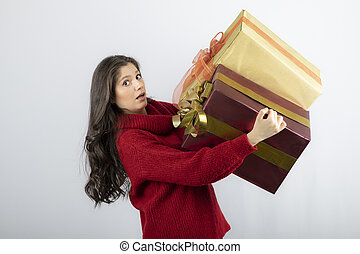 Young woman in red sweater carrying Christmas presents
