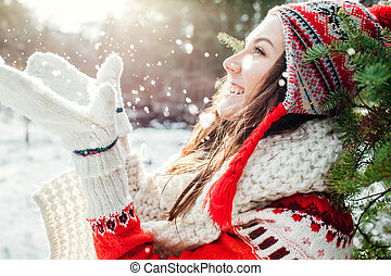 Young woman in red sweater throws snow. Winter activities.