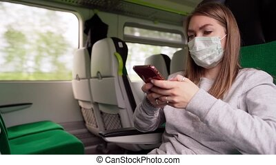 Young Woman In Respirator Mask Using Smartphone In A Train. ...