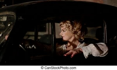 Young woman in retro car indoors.