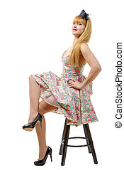 Young woman in retro floral dress, sitting on stool