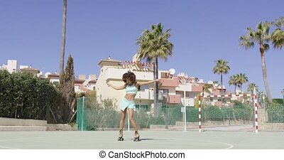 Young woman in roller skates dancing