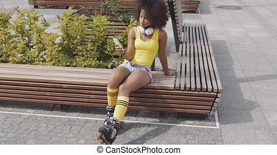 Young woman in rollers with smartphone