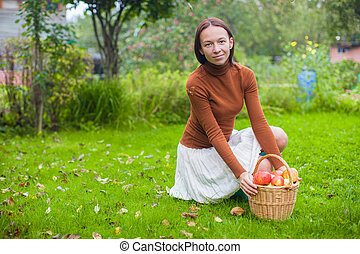 Young woman in rubber boots holding the straw basket with red apples at autumn time