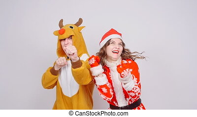 Young woman in santa claus hat and man in carnival costume of deer. Fun, holiday and christmas