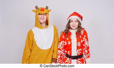 Young woman in santa claus hat and man in carnival costume...