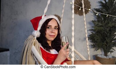 Young woman in Santa Claus suit with glass of champagne sitting on hammock. Attractive female in Christmas hat swinging on hammock chair. Concept of Christmas celebration at home