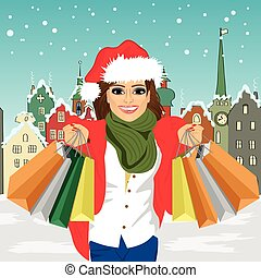 young woman in santa hat holding shopping bags in front of small town