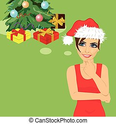 young woman in santa hat looking up thinking about gifts under christmas tree