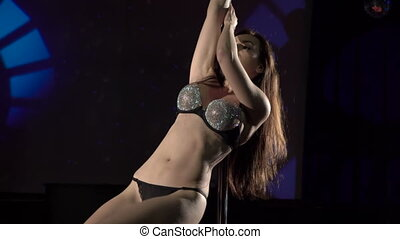 Young woman in sexy lingerie performs pole dance on night club lighted stage