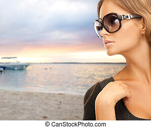 young woman in shades over sea shore background - people,...