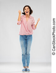 young woman in shirt and jeans celebrating success