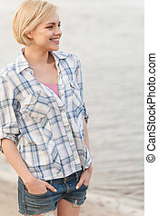 Young woman in shirt and jeans standing on sea shore. blond girl looking at water on sand and smiling