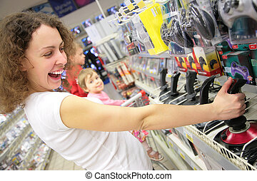 young woman in shop plays with joystick