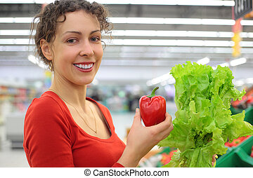 young woman in shop with red sweet pepper and salad