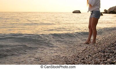 Young woman in shorts walking along the beach of the Adriatic Sea