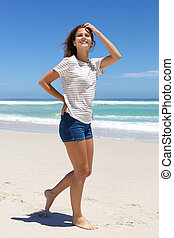 Young woman in shorts walking on the beach