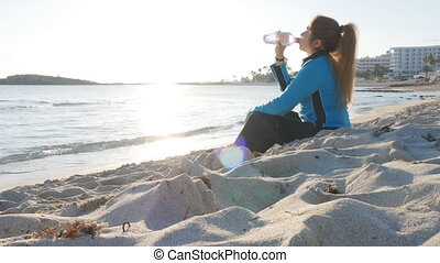 Young woman in sport clothes drinking water after workout on the beach