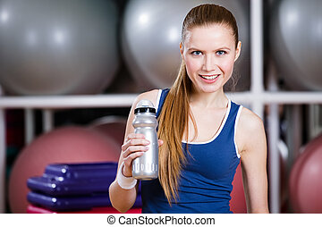Young woman in sportswear holds a water bottle