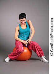 young woman in sportswear sits on orange ball
