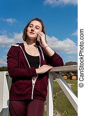 woman in sportswear talking by phone