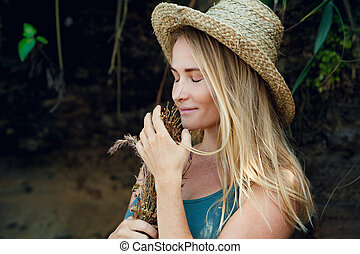 Young woman in straw hat hold bouquet of dried wildflowers