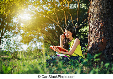 woman in stress situation when reading a book in the park