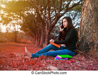 young woman in stress situation when talking on mobile phone in park