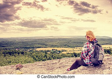 Young woman in striped jacket take a rest on rocky summit