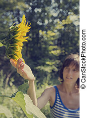 Young woman in stripped shirt touching a beautiful blooming sunflower