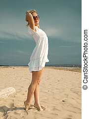 woman in summer dress standing on sand