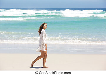 Young woman in summer dress walking on the beach