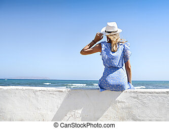 Young woman in summer dress with straw hat