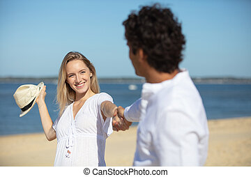 young woman in summer straw hat flirts with man