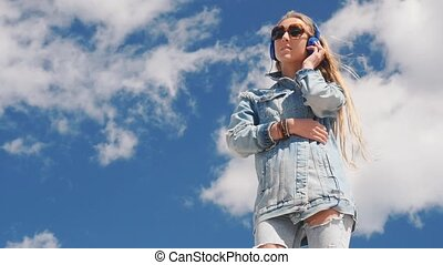 Young woman in sunglasses and jeans wear listening music with headphones outdoors