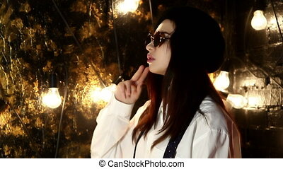 Young woman in sunglasses, beret and shirt on background wall with light bulbs