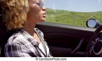 Young woman in sunglasses driving her car