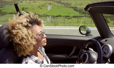Young woman in sunglasses driving her car through a scenic...