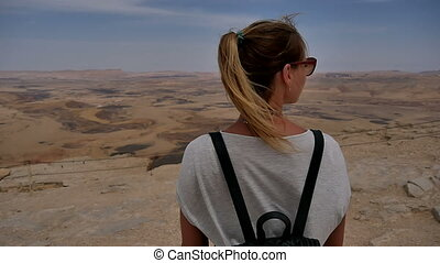 Young woman in sunglasses enjoying the stone desert view on cliff's edge