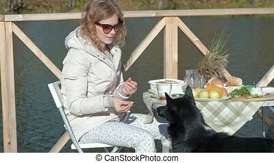 young woman in sunglasses, in warm clothes, sitting at a table, drinking tea, eating pancakes with jam, feeding a dog, picnic by the river on a wooden bridge, weekend, cold weather, camping, tourism