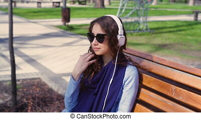 young woman in sunglasses listening to music with headphones in the park on a bench